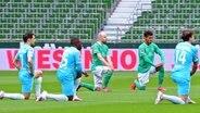 Zeichen gegen Rassismus: Die Spieler von Werder Bremen und Wolfsburg knien vor dem Anpfiff der Bundesliga-Partie am Mittelkreis. © Witters Foto: Valeria Witters
