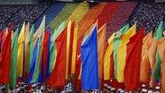 Abschlussfeier im Olympiastadion, das olympische Feuer im Hintergrund, Sportler mit bunten Fahnen im Vordergrund © ullstein bild - Schlage