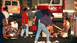 Helfer bemühen sich um die am Boden liegenden Opfer einer schweren Explosion im Zentrum der Olympia-Stadt Atlanta. © picture-alliance / dpa