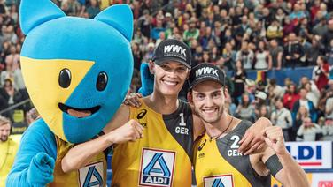 Clemens Wickler (r.) und Julius Thole jubeln mit dem Maskottchen bei der Beachvolleyball-WM in Hamburg