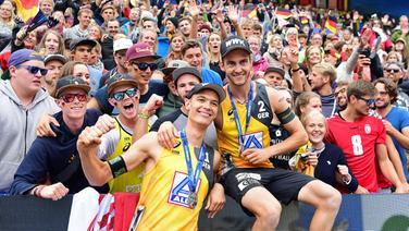 Julius Thole (l.) und Clemens Wickler mit ihren Silbermedaillen und den Fans der Beachvolleyball-WM in Hamburg.