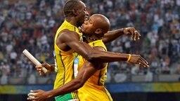 Usain Bolt und sein Teamkollege Asafa Powell feiern ihre Goldmedaille im 4x100-m-Lauf. © AP Foto: Mark J. Terrill