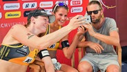 Julius Brink (r.) mit dem Beachvolleyballduo Julia Sude (l.) und Chantal Laboureur © imago images/Beautiful Sports