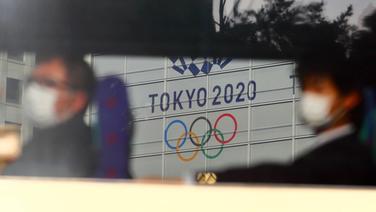 Zugpassagiere mit Atemschutz vor dem Olympia-Banner in Tokio © imago images/AFLO