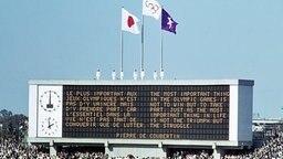Eröffnungsfeier im Olympiastadion von Tokio: - die Olympische Fahne wird auf der Anzeigetafel gehisst; auf dieser steht das Olympische Motto von Baron Pierre de Coubertin © ullstein bild
