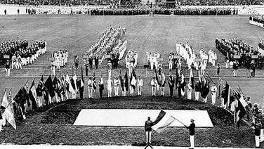 Auf dem Rasen des Amsterdamer Olympiastadions haben die Fahnenträger und die teilnehmenden Mannschaften Aufstellung genommen. © picture-alliance/ dpa