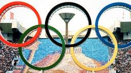 Eröffnungsfeier der XXII. Olympischen Sommerspiele am 19.07.1980 im Moskauer Lenin-Stadion: Ein Gestell mit den fünf Olympischen Ringen wird in die Arena gerollt. © picture-alliance / dpa