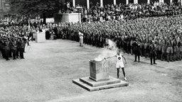 Ein Läufer entzündet das olympische Feuer. © picture-alliance / IMAGNO/Austrian Archives