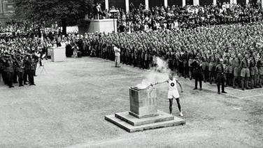Ein Läufer entzündet das olympische Feuer im Berliner Lustgarten. © picture-alliance / IMAGNO/Austrian Archives