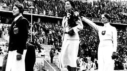 Die Reproduktion einer Aufnahme vom August 1936: Siegerehrung für die Fechterinnen im Berliner Olympiastadion 1936 © picture-alliance/ dpa