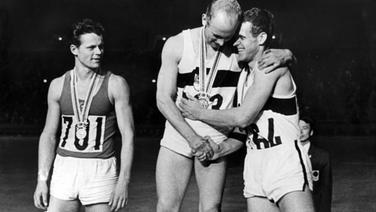 Zehnkampf-Olympiasieger Willi Holdorf (M.) bei der Siegerehrung in Tokio 1964 © picture alliance / dpa