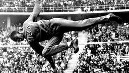 Berlin 1936: Hochspringer Cornelius Johnson (USA) überspringt die Qualifikationshöhe von 1,85 m im Trainingsanzug. © picture-alliance / dpa