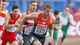 Der Sprinter Sven Knipphals erhält den Staffelstab von Julian Reus