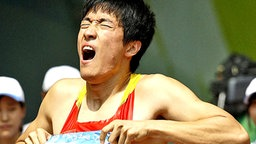 Liu Xiang mit schmerzverzerrtem Gesicht. © AP Foto: David J. Phillip