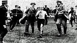 Der Italiener Dorando Pietri (M.) wird wegen unerlaubter Hilfestellung disqualifiziert © picture-alliance/ dpa