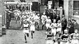 Die Läufer verlassen nach Start zum Marathonlauf das Olympiastadion. © picture-alliance/ dpa