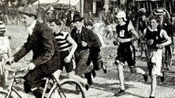 Marathonläufer und Begleiter auf dem Rad beim Olympia-Wettkampf in Paris © Popperfoto/Getty Images
