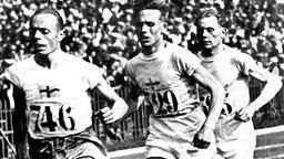 Der finnische Läufer Paavo Nurmi (l.) siegt bei Olympia 1924 in in Paris im 5000-Meter-Lauf. © picture-alliance/ dpa