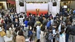 Menschenmassen im japanischen Bahnhof Sendai, wo das Olympische Feuer präsentiert wird. © imago images / Kyodo News