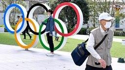 Menschen vor den Olympischen Ringen im Olympiapark in Tokio © imago images/Laci Perenyi