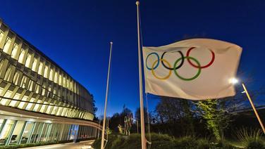 Die olympische Flagge weht am Eingang des Internationalen Olympischen Komitees © picture alliance/dpa/KEYSTONE Foto: Jean-Christophe Bott