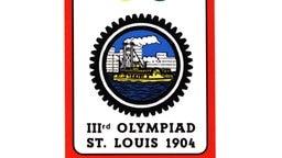 Das Olympialogo der 3. Olympischen Spiele in St. Lous 1904. Im Mittelpunkt dieser klaren graphischen Darstellung befindet sich in einem zahnkranzartig gestalteten Kreis eine Hochhaussilhouette mit einem Raddampfer davor. © picture-alliance / dpa