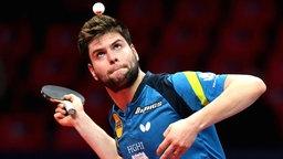 Tischtennisspieler Dimitrij Ovtcharov schaut bei der Angabe auf den Ball.