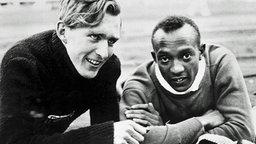 Der Deutsche Luz Long und der Amerikaner Jesse Owens beobachten ihre Konkurrenten beim Weitsprung. © ullstein bild - ullstein bild