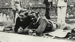 Der Deutsche Luz Long und der Amerikaner Jesse Owens beobachten ihre Konkurrenten beim Weitsprung. © picture-alliance / akg-images
