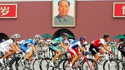 Die Radrennfahrer passieren ein Portrait von Mao Zedong. © AP Foto: Greg Baker