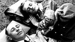 """Berlin 1936: Zwei Programm-Verkäufer machen ein """"Nickerchen"""" auf dem Rasen. © picture-alliance / akg-images"""