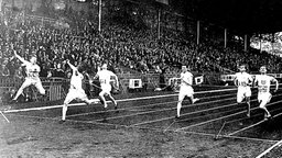 Das Finish im 200-m-Lauf der Männer bei den Olympischen Spielen in Paris: USA-Sprinter Jackson Scholz (2.v.l) wirft sich als erster in die Zielschnur. © picture-alliance/ dpa