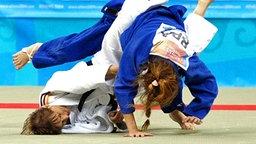 Die Deutsche Susann Schuetzel (oben) hat die Französin Sandrine Aureires im Griff. Die sehbehinderte Diplom-Sozialpädagogin Susann Schützel vom JC Frankfurt (Oder) glänzt in der Klasse bis 52 kg glänzt bei den Paralympics in Athen am 18.09.2004 gegen die die fünffache Welt- und Europameisterin aus Frankreich mit einem vorzeitigen Sieg (Ippon) und erkämpft bei der Judo-Premiere der Frauen auf Anhieb die Goldmedaille. © (c) dpa - Sportreport