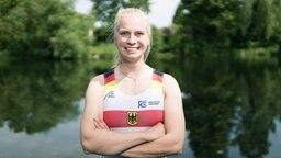 Die Ruderin Frieda Hämmerling steht in Ruder-Outfit vor einem Gewässer und blickt fröhlich in die Kamera.
