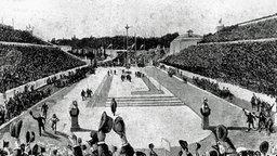 Der griechische Bauernsohn Spyridon Louis wird auf den letzten Metern im Marmorstadion von Athen von Kronprinz Konstantin und Prinz Georg begleitet, während die Zuschauer im vollbesetzten Stadion jubeln und die Hüte schwenken. © ullstein bild - ullstein bild