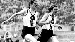 Berlin 1932: Die deutsche Sprinterin Marie Dollinger (l.) übergibt den Staffelstab beim letzten Wechsel der 4x100-m-Staffel der Frauen an Ilse Dörffeldt. © picture-alliance / dpa