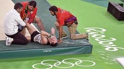 Turner Andreas Toba wird am Boden behandelt. © dpa