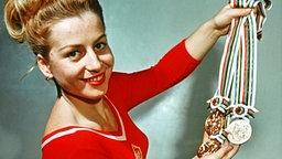 Vera Caslavska zeigt ihre drei Goldmedaillen, die sie bei den Olympischen Sommerspielen 1964 in Tokio gewonnen hat. © picture-alliance/ dpa