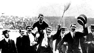 100-m-Sieger Reginald Walker (Südafrika) wird auf den Schultern seiner begeisterten Landsleute aus dem Stadion getragen. © picture-alliance / akg-images