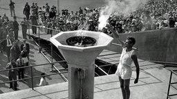 John Mark, ein 22 Jahre alter Medizinstudent des St. Mary Hospital Paddington, entzündet die Olympische Flamme im Wembley-Stadion. © ullstein bild - TopFoto