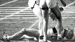 Der estnische Sportler Rein Aun und Horst Beyer bemühen sich um den nach dem Zieleinlauf des 1.500-m-Laufes vor Erschöpfung gestürzten Willi Holdorf © picture-alliance / dpa