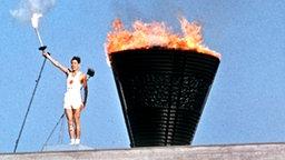 Yoshinori Sakai, der Schlussläufer der Fackelstafette, beim Entzünden des Feuers © picture-alliance / dpa