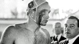 Der ungarische Spieler Ervin Zador (l) wird im Wasser von einem UdSSR-Spieler angegriffen und so verletzt, dass Blut aus einer Wunde am rechten Auge fließt. © picture-alliance / dpa