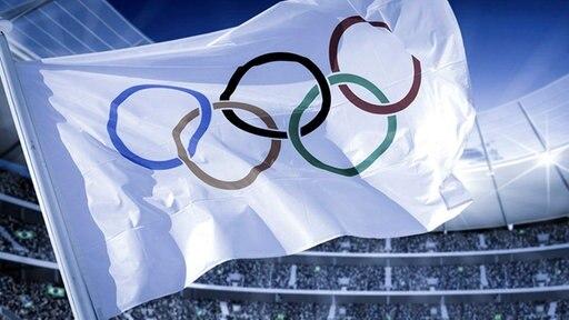 Die olympische Fahne weht in einer Sportarena (Bildmontage)