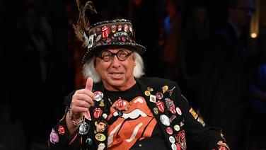 Ulrich Schröder sitzt in Stones-Klamotten auf einem Stuhl und zeigt einen Daumen in die Kamera- © NDR