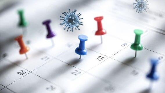 Corona-Viren schweben über einem Kalender. Symbolbild © fotolia Foto: psdesign1, Brian Jackson