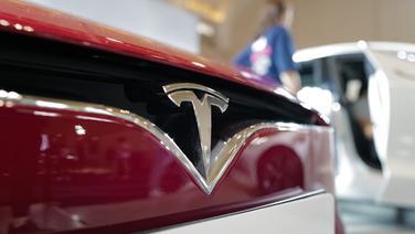 Blick auf das Logo von einem Tesla Auto. | picture alliance