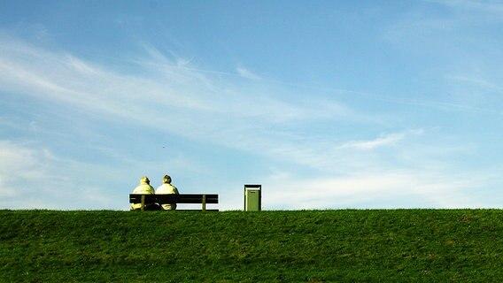 Zwei Männer sitzen auf einer Bank auf einem Deich. © photocase.de Fotograf: micjan