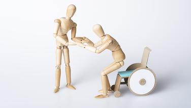 Ein stehendes Holzmännchen hilft einem anderen Holzmännchen aus dem Rollstuhl (Themenbild) | fotolia