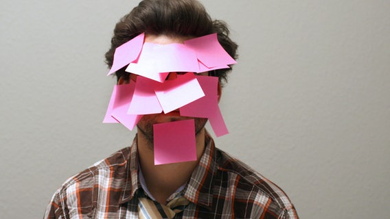 Ein Mann hat sein ganzes Gesicht mit rosafarbenen Post-it-Zetteln zugeklebt. © photocase Foto: Bastografie